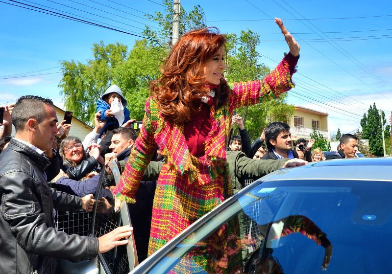Argentina's President Cristina Fernandez (C), greets her supporters after casting her vote in the school of Our Lady of Fatima, in the city of Rio Gallegos, ...