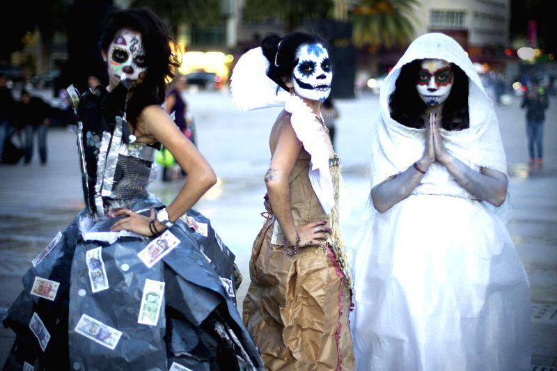 Art students dressed with Catrina's costumes made with recycled materials pose to celebrate the Day of the Dead in Mexico City, capital of Mexico, on Oct. 29, ...