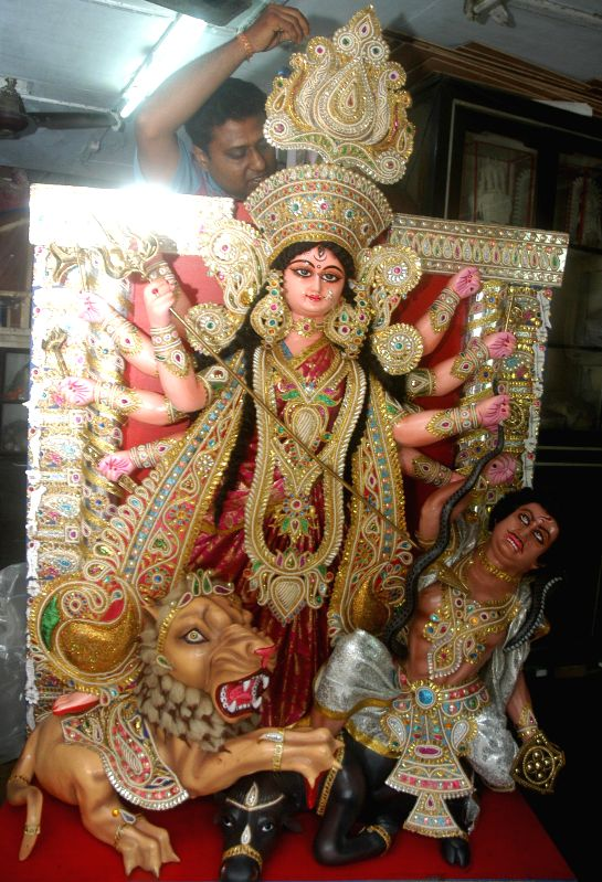 Artist Koushik Ghosh, gives finishing touches to an Italy bound idol of Goddess Durga at a Kumartoli workshop in Kolkata on Aug 3, 2014. - Koushik Ghosh