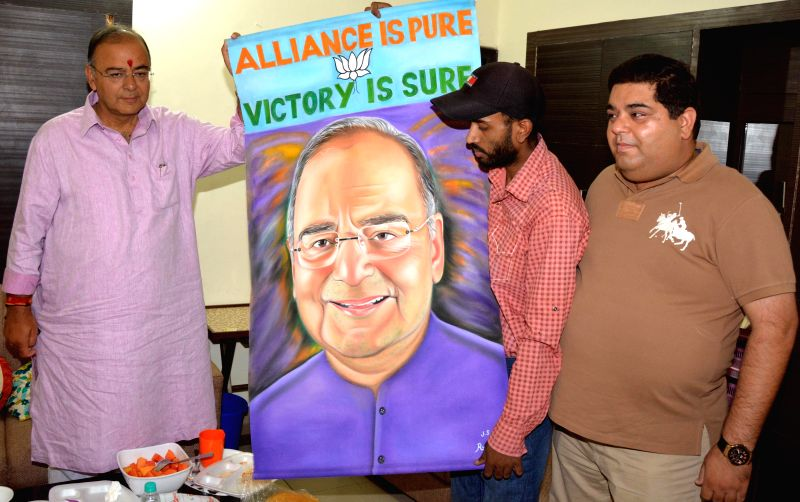 Artist Rubal presents a painting of BJP candidate for 2014 Lok Sabha Election from Amritsar, Arun Jaitley to the politician in Amritsar on April 29, 2014. - Rubal