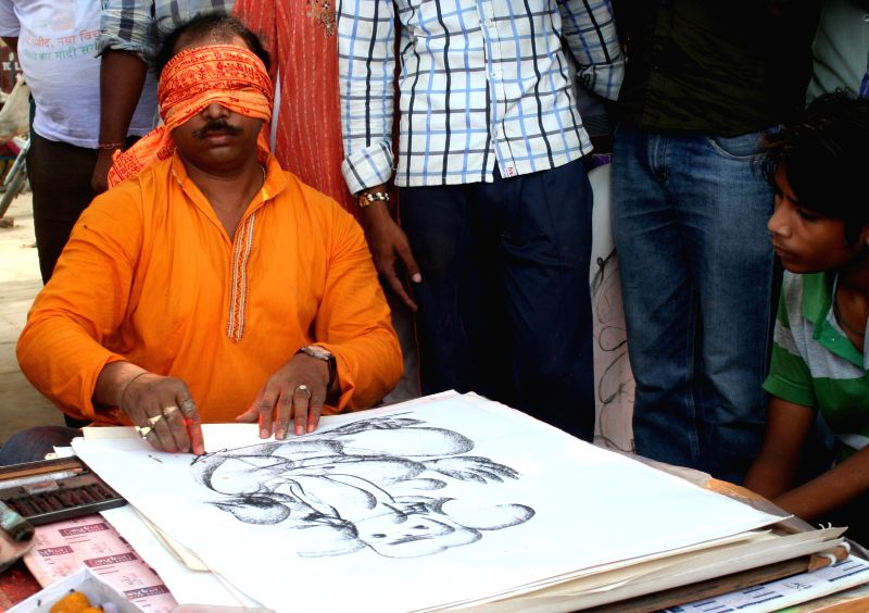 Artist Vijay, a Limca book record holder, sketches a picture of lord Ganesh blindfoldedly on the banks of Ganga river ahead of Ganesh Chaturthi in Varanasi on Aug 28, 2014. - Vijay