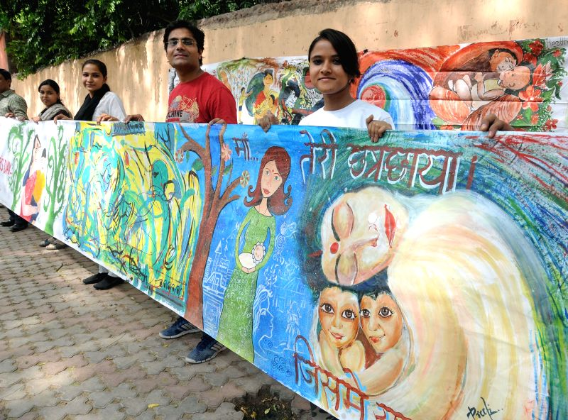 Artists and embers of Health Education and Environment Awareness Society hold a picture painted by them on Mother's Day at Jantar Mantar in New Delhi on May 11, 2014.