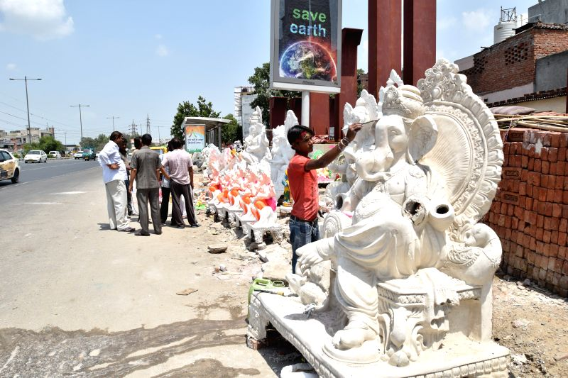 Artists give final touches to a Ganesh idol ahead of Ganesh Chaturthi at a makeshift workshop in New Delhi on Aug 17, 2014.