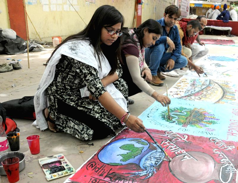 Artists paint pictures themed on population at Jantar Mantar on the eve of World Population Day in New Delhi on July 10, 2014.