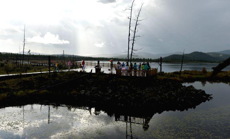 Tourists are seen near Dujuan Lake in Arxan City, north China's Inner Mongolia Autonomous Region, Aug. 18, 2014.