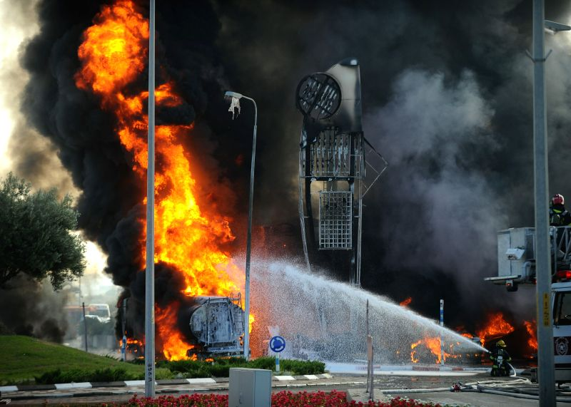 ASHDOD (ISRAEL), July 11, 2014 Israeli firefighters extinguish a fire that broke out after a rocket hit a gas station in Ashdod, southern Israel, on July 11, 2014. On Friday morning, one .