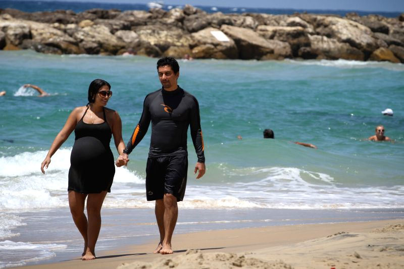 An Israeli couple walk on the shore of the Mediterranean sea near southern Israeli town Ashkelon, 10 kilometers north of the Gaza Strip, on July 26, 2014. Israeli .