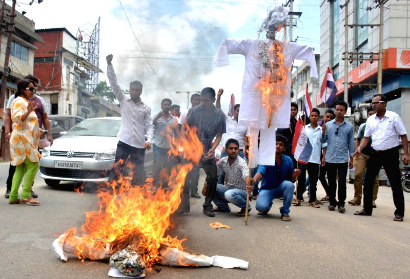 Asom Gana Parishad (AGP) activists burn effigies of Assam Chief Minister Tarun Gogoi during a demonstration against hike in prices of essential commodities in Guwahati on July 4, 2014. - Tarun Gogoi