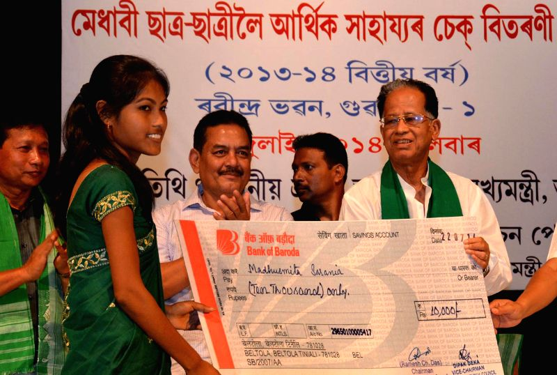 Assam Chief Minister Tarun Gogoi distributes scholarship cheques to the meritorious students of Sarania Kachari community during a programme at at Rabindra Bhawan in Guwahati on July 22, 2014. - Tarun Gogoi