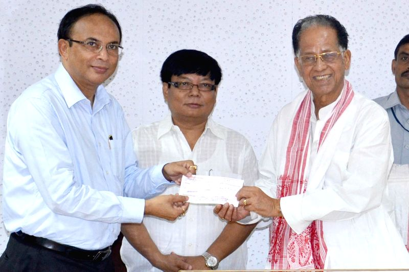 Assam Chief Minister Tarun Gogoi hands over a cheque for 5 lakh towards Student and Youth Welfare to the representatives of Dibrugarh University for career coaching at Assam Secretariat, Dispur in ... - Tarun Gogoi
