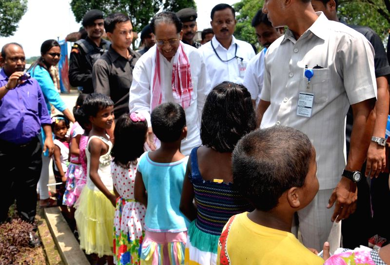 Assam Chief Minister Tarun Gogoi interacts with children during his visit to SOS children's village at Azara in Guwahati on July 9, 2014.