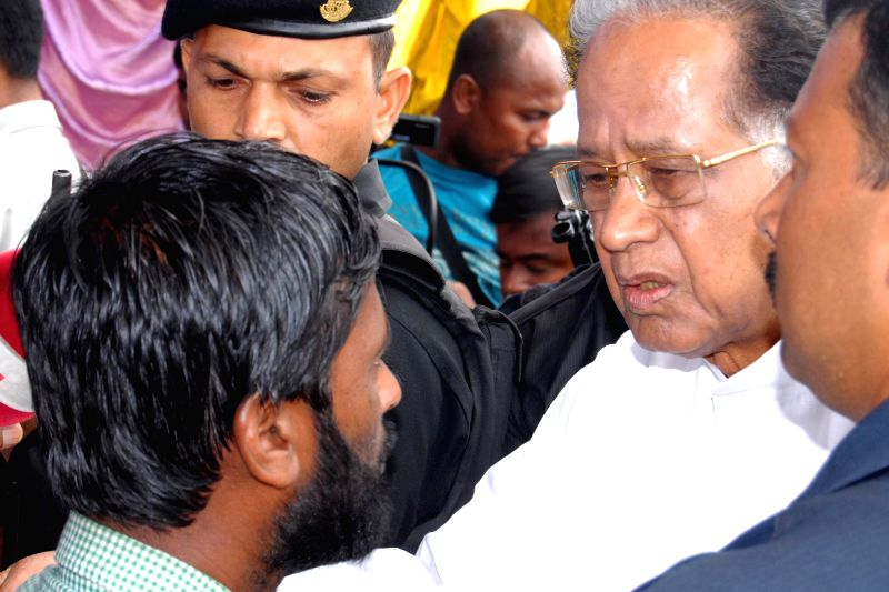 Assam Chief Minister Tarun Gogoi interacts with a man during his visit to Narayanguri Relief Camp setup to provide shelter to those who fled their villages after recent violence in Bodoland ...