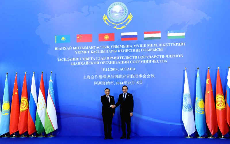 Chinese Premier Li Keqiang (L) is greeted by his Kazakh counterpart Karim Masimov as attending the 13th prime ministers' meeting of the Shanghai Cooperation Organization (SCO) in Astana, ...