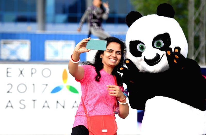 ASTANA, June 6, 2017 - A woman takes selfie with a dancer wearing panda costume during a performance of Sam Ruk dance group from Eurasian University in Astana, Kazakhstan, June 5, 2017.
