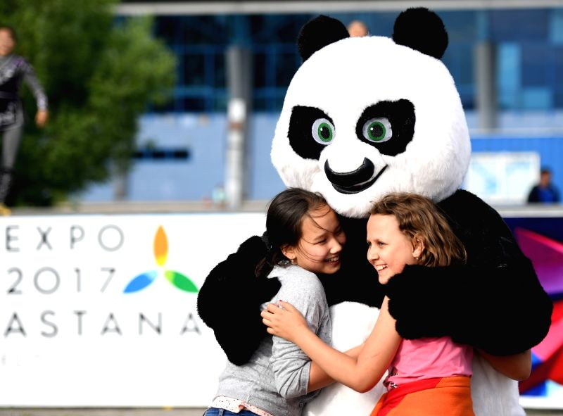 ASTANA, June 6, 2017 - Girls play with a dancer wearing panda costume during a performance of Sam Ruk dance group from Eurasian University in Astana, Kazakhstan, June 5, 2017.