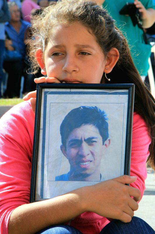 A child holds an image during a ceremony in remembrance of the victims of the fire in the Ycua Bolanos supermarket, in Asuncion, capital of Paraguay, on Aug. 1, ...