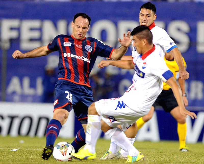 Nacional's Jose Caceres (R) vies for the ball with Mauro Matos (L) of San Lorenzo, during their first-leg final match of the 2014 Libertadores Cup, held at ...
