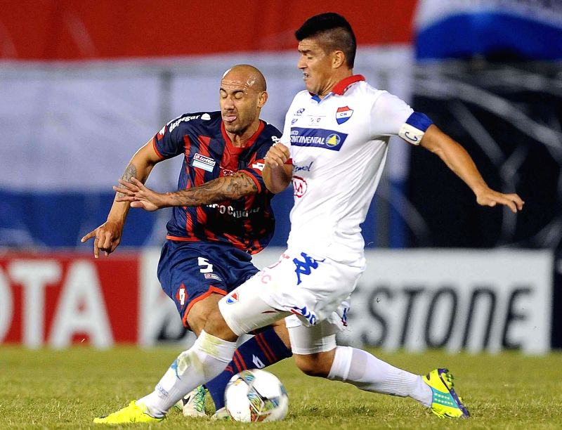 Nacional's Jose Caceres (R) vies for the ball with Juan Mercier (L) of San Lorenzo, during their first-leg final match of the 2014 Libertadores Cup, held at ...