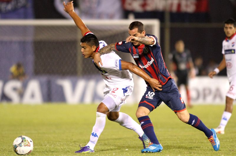 Nacional's Ramon Coronel(L) vies for the ball with Leandro Romagnoli(R) of San Lorenzo during their first-leg final match of the 2014 Libertadores Cup at Defensores
