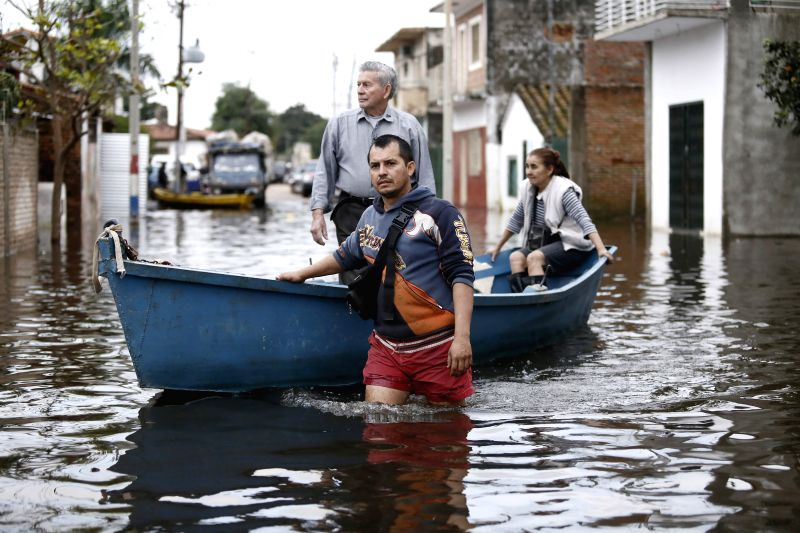 People move in a boat through a flooded street in the Tacumbu neighborhood, in Asuncion, capital of Paraguay, on July 1, 2014. Thousands of people have been ...