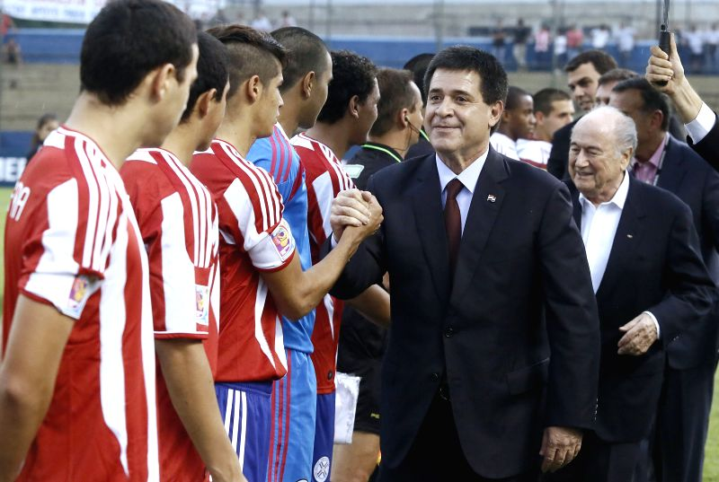Paraguay's President Horacio Cartes (C) and FIFA President Joseph Blatter (R) greet players during the inauguration of the South American Championship U17 in ...