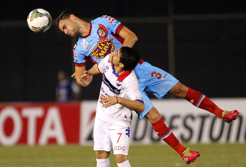 Nacional's Julian Benitez (Bottom) vies for the ball with Leandro Gonzalez of Arsenal during the first leg quarterfinals match of the Libertadores Cup 2014 held in ..