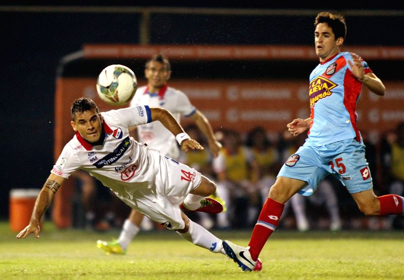 Nacional's Marcos Melgarejo (L) vies for the ball with Damian Perez of Arsenal during the first leg quarterfinals match of the Libertadores Cup 2014 held in the ...