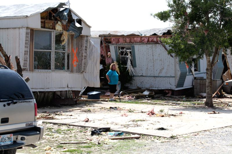 A woman surveys damage at the Billy Bob Trailer Park in Athens in Alabama, the United States, April 29, 2014. Authorities said on Monday that 15 people were killed .