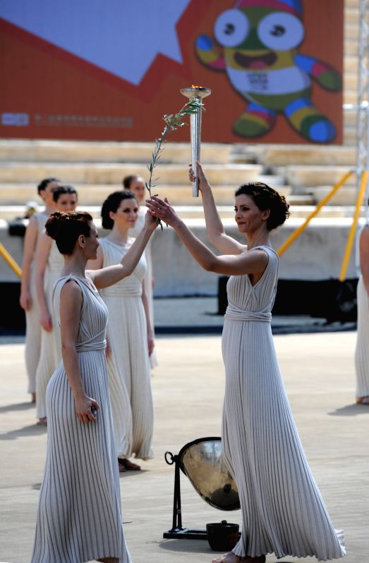 Greek actress Katerina Lehou (R), playing the role of high priestess, holds the torch with the Olympic Flame during a handover ceremony at Panathenaean Stadium in .. - Katerina Lehou