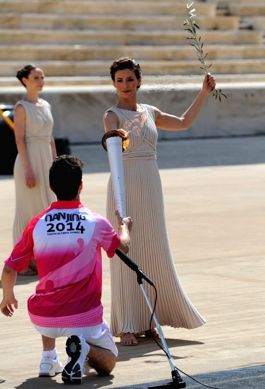 Greek actress Katerina Lehou(R), playing the role of high priestess, lights the first leg of the torch relay during a handover ceremony at Panathenaean Stadium in .. - Katerina Lehou