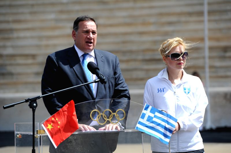 President of the Hellenic Olympic Committee Spyros Capralos(L) makes a speech during during a handover ceremony at Panathenaean Stadium in Athens, Greece, April 30,