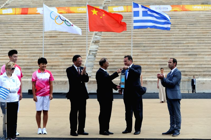 President of the Hellenic Olympic Committee Spyros Capralos (2nd R) hands the safety lantern containing the Youth Olympic flame to President of the Chinese Olympic .