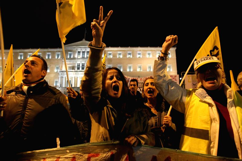 Athens (Greece): Protesters shout slogans during a parliament meeting for a vote on the country's 2015 budget in Athens on Dec. 7, 2014. Greece's conservative government rejected demands by rescue ...