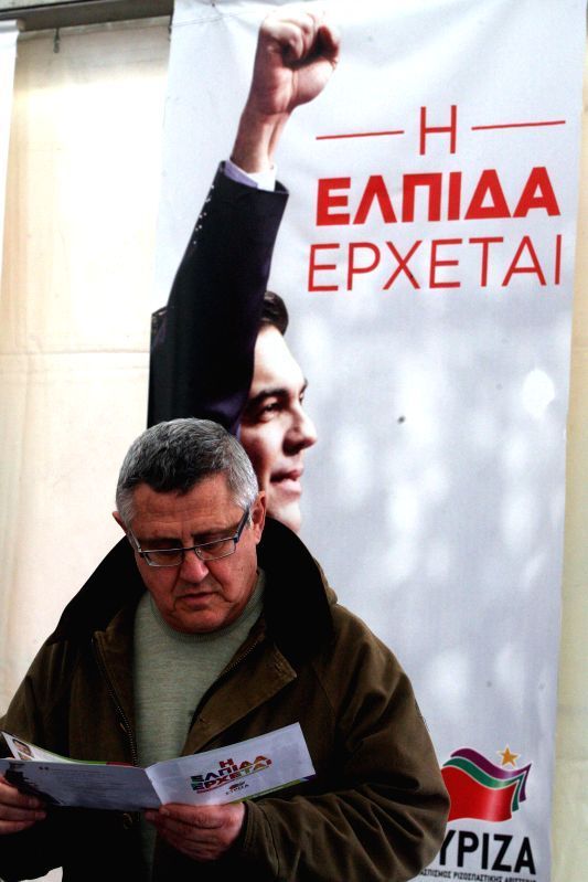 A man reads a leaflet outside an election kiosk of left-wing Syriza party in Athens, Greece, Jan. 20, 2015. Greece will hold general elections on  Jan. 25. ...