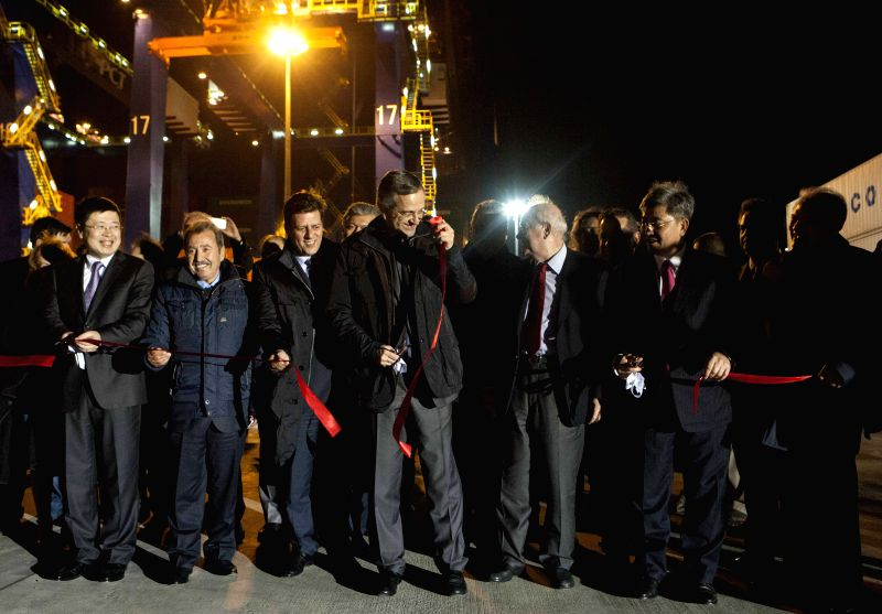 Greek Prime Minister Antonis Samaras (C) and Chinese Ambassador to Greece Zou Xiaoli (1st L) cut the ribbon during the starting ceremony of the expansion of Pier III - Antonis Samaras