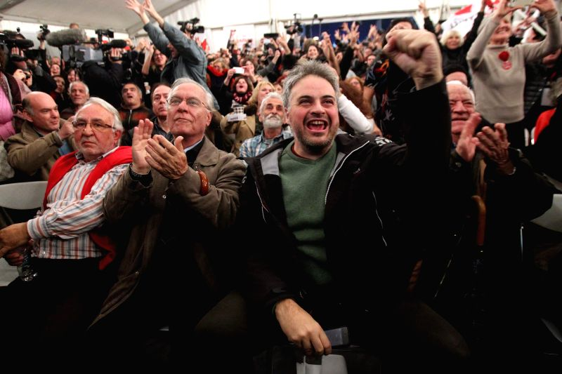 People react as they watch the exit poll results at the election kiosk of Left SYRIZA party in Athens, Greece, Jan. 25, 2015. Greek Radical Left SYRIZA party leads ..