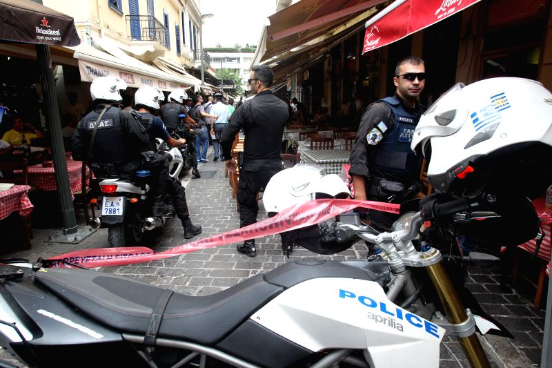 Greek policemen investigate at the cordoned off area around a bank robbery shootout in central Athens, Greece, July 16, 2014. Greek police have arrested the leader ..