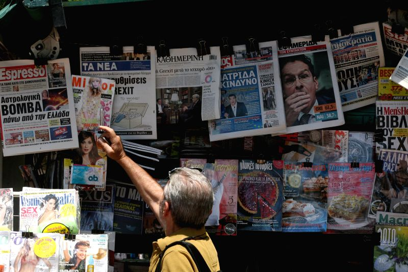 Pedestrians gaze at press headlines in Athens, Greece, July 6, 2015. Greek President Prokopis Pavlopoulos convened political leaders for a meeting to design new ...