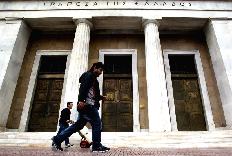 People pass in front of Greek banks in Athens, Greece, March 9, 2015. Greek government will submit a list of reforms at Monday's critical Eurogroup meeting in ...