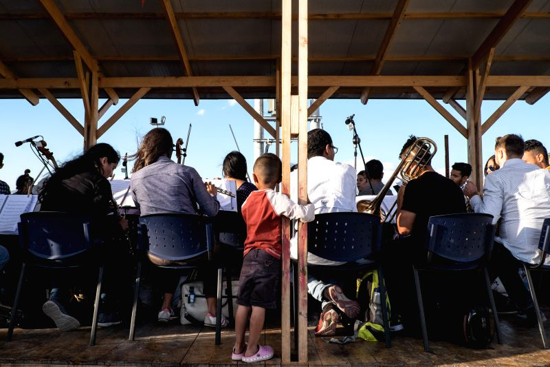 ATHENS, May 10, 2017 - A Refugee child stands behind musicians of the Municipal Youth Orchestra of Caracas from Venezuela during a concert at?Skaramangas refugee camp near Piraeus, Greece, on May 10, ...