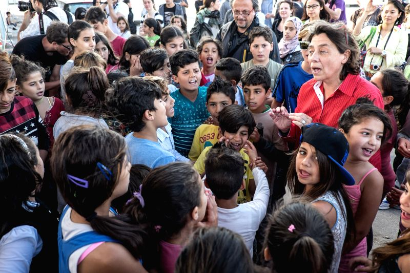 ATHENS, May 10, 2017 - Refugee children sing a song with the performance given by the Municipal Youth Orchestra of Caracas from Venezuela at?Skaramangas refugee camp near Piraeus, Greece, on May 10, ...