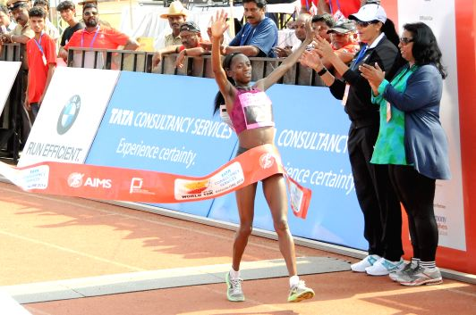 Athlete Lacy Kabuu celebrates at the finishing line during TCS World 10K Bangalore at Kanteerava Stadium in Bangalore on May 18, 2014.