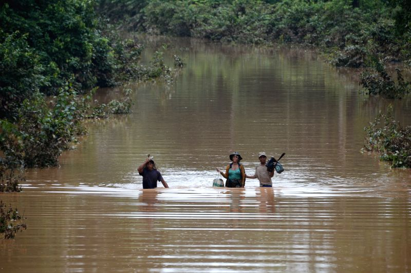 ATTAPEU, July 26, 2018 - Villagers wade through flood after an under-construction dam collapsed in Attapeu province, Laos, on July 26, 2018. The under-construction Xepian-Xe Nam Noy hydropower dam ...