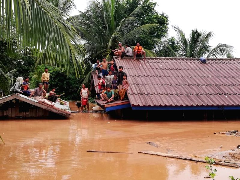 ATTAPEU (LAOS), July 24, 2018 Villagers are seen stranded on rooftops of houses after an under-construction dam collapsed in Attapeu, Laos, on July 24, 2018. At least two people are ...