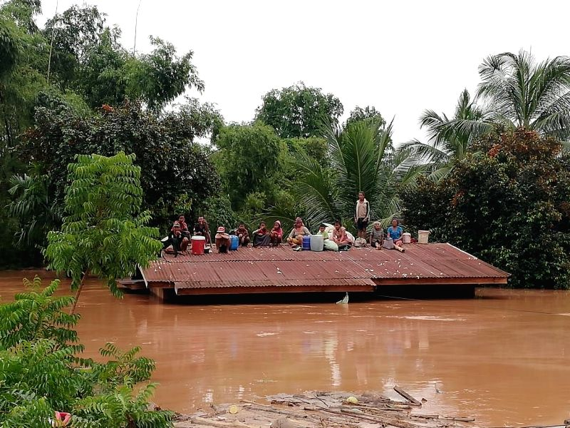 :ATTAPEU (LAOS), July 24, 2018 Villagers are seen stranded on rooftop of a house after an under-construction dam collapsed in Attapeu, Laos, on July 24, 2018. At least two people are ...