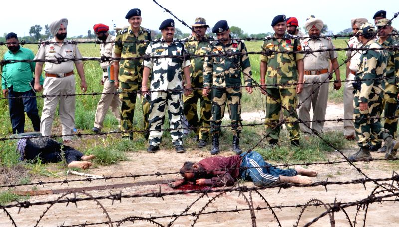 BSF officials recover 12 kg heroine from alleged Pakistani smugglers who were killed in an encounter near BOP Rattan Khurd in Attari, Punjab on March 29, 2015.
