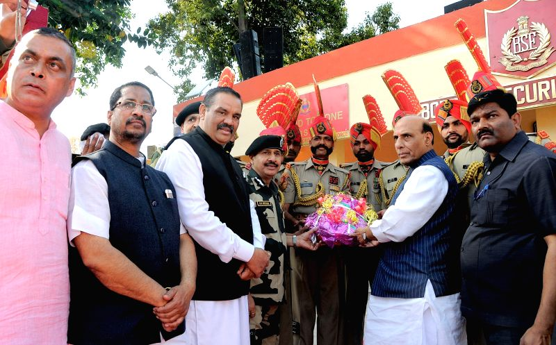 Union Home Minister Rajnath Singh, Punjab Chief Minister Parkash Singh Badal and other leaders giving fruit basket to BSF jawan's after inaugurating the viewer's gallery at Attari ... - Parkash Singh Badal