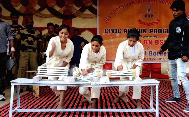 Village girls breaking slabs to show their strength and skill of self defense during a civic action programme organized by Border Security Force at Attari on Nov 22, 2014.