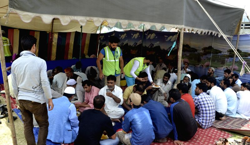 Attendants of patients at the district hospital sit in a queue to collect food distributed by Relief Committee Jamaat-e-Islami as authorities imposed a strict curfew in most parts of ...