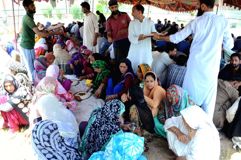 Attendants of patients at the SKIMS hospital sit in a queue to collect food distributed by Relief Committee Anchar Soura as authorities imposed a strict curfew in most parts of Kashmir ...